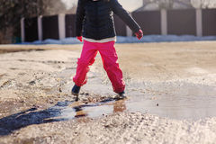 Child girl in waterproof pants jumping in puddle on winter walk Royalty Free Stock Photos