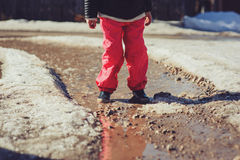 Child girl in waterproof pants running and jumping in puddle on early spring walk Stock Photo