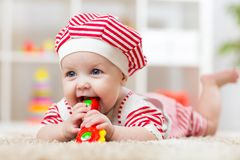 Child girl weared costue biting a toy lying on a carpet at home Royalty Free Stock Photo