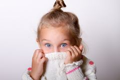 Child girl wearing knited sweater hiding her face in collar look Royalty Free Stock Images