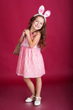Child girl is wearing pink ears with gifts Stock Image
