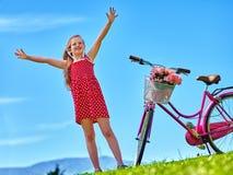 Child girl wearing red polka dots dress rides bicycle . Stock Image