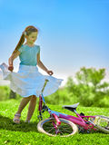 Child girl wearing red polka dots dress rides bicycle into park. Royalty Free Stock Photos
