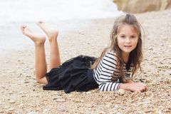 Child girl is wearing stripped dress on the beach Stock Photography