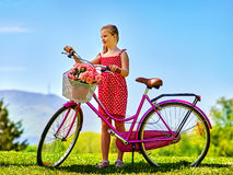 Child girl wearing sundress rides bicycle into park. Stock Photos