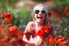 Child girl is wearing sunglasses in spring field with poppies. Cute smiling child girl with long blonde hair is wearing sunglasses with bouquet of flowers in red stock photo