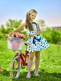 Child girl wearing white polka dots dress rides bicycle into park. Bikes cycling girl. Child girl wearing white polka dots dress rides bicycle with pink flowers stock photos