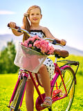 Child girl wearing white polka dots dress rides bicycle into park. Royalty Free Stock Images