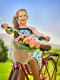 Child girl wearing white polka dots dress rides bicycle into park. Stock Photos