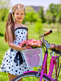 Child girl wearing white polka dots dress rides bicycle . Stock Photography