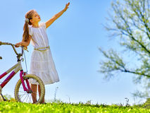Child girl wearing white skirt rides bicycle into park. Royalty Free Stock Images