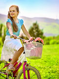 Child girl wearing white skirt rides bicycle into park. Stock Photography