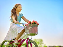 Child girl wearing white skirt rides bicycle into park. Royalty Free Stock Photo