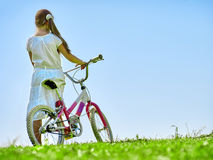 Child girl wearing white skirt rides bicycle into park. Royalty Free Stock Image