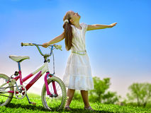 Child girl wearing white skirt rides bicycle into park. Stock Image