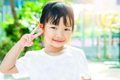 Child girl wearing a white t-shirt poses and is smiling brightly stock image
