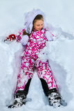 Child girl wearing winter clothes lying in snow . Royalty Free Stock Photography