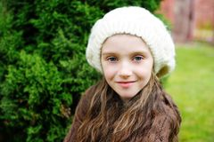 Child girl in white cap, close-up portrait. Close-up portrait of adorable child girl wearing white cap Stock Photos