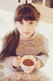 Child girl with a white cup of hot drink Stock Photos