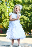 Child girl in white gown, happy childhood concept, summer season in city park Royalty Free Stock Images