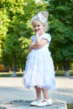 Child girl in white gown posing, happy childhood concept, summer season in city park Stock Images