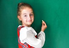 Child girl whritin with chalk on school board. stock image