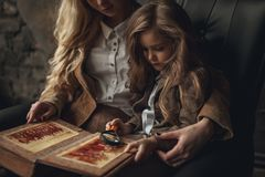 Child girl with woman in image of Sherlock Holmes sits and looks photoalbum with magnifier on background of old interior. Child girl with women in image of Royalty Free Stock Photos