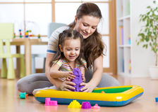 Child girl and woman mould with kinetic sand in playschool or daycare Royalty Free Stock Photo