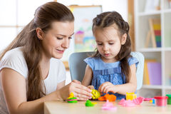 Child girl and woman playing colorful clay toy at nursery or kindergarten Stock Photos