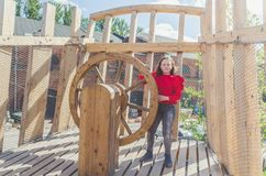 Girl on a wooden Playground in the form of a pirate ship. A child, a girl on a wooden Playground in the form of a pirate ship at the helm stock photos
