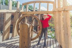 Girl on a wooden Playground in the form of a pirate ship. A child, a girl on a wooden Playground in the form of a pirate ship at the helm royalty free stock image