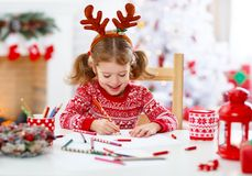 Child girl writing letter santa home near Christmas tree. Child girl writing letter santa home near the Christmas tree Stock Photos