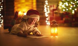 Child girl writing letter santa home near Christmas tree Royalty Free Stock Photography