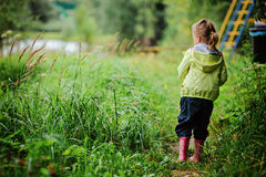 Child girl in yellow jacket and rubber boots walking in summer Royalty Free Stock Photos