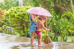 Child girls cleaning up the path, outdoors, during the rain Royalty Free Stock Photo