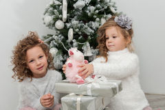 Child girls with gifts near Christmas tree Royalty Free Stock Photos