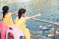 Child girls having fun to feed and give food to fish Stock Photo