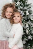Child girls near Christmas tree Royalty Free Stock Photo