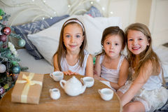 Child girls wake up in her bed in Christmas morning Stock Photos
