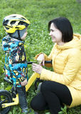 A child gives flowers to his mother, for a walk, a boy on a bicycle Royalty Free Stock Images