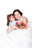Child gives flowers to mother in bed stock image