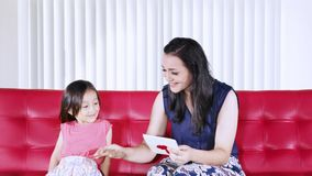 Child gives greeting card to mother at home. Cute little girl giving a greeting card to her mother on the red sofa in the living room at home