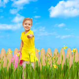 Child giving flower sky blue summer garden Royalty Free Stock Photo