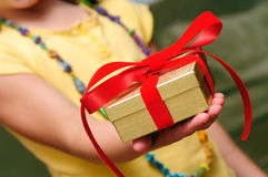 Child Giving Gift. In golden box with red ribbon Royalty Free Stock Image