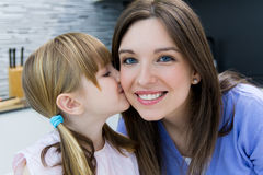Child giving a kiss to his mother on the cheek Royalty Free Stock Image