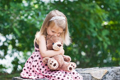 Child giving teddy a hug and kiss. Stock Image