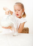 Child with glass pitcher milk. Little girl drinking milk at home Stock Photos
