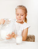 Child with glass pitcher milk. Little girl drinking milk for breakfast Royalty Free Stock Photography