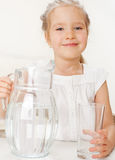 Child with glass pitcher water. Little girl drinking water at home Royalty Free Stock Images