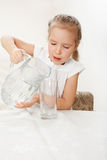 Child with glass pitcher water. Little girl drinking water at home Royalty Free Stock Photography